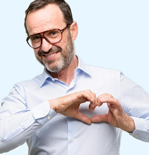 smiling man making heart with hands over chest