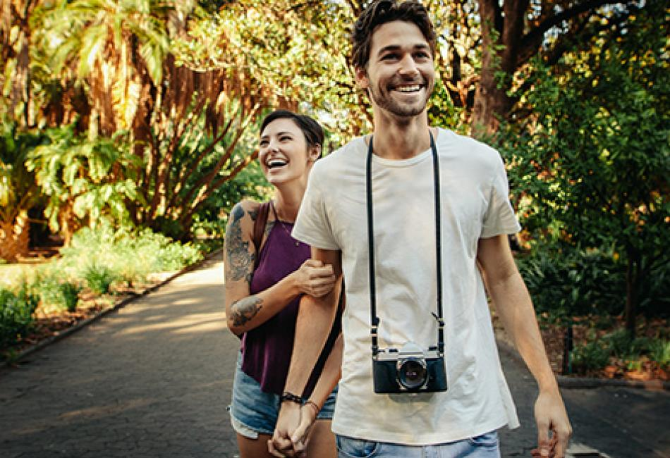 young couple walking through park